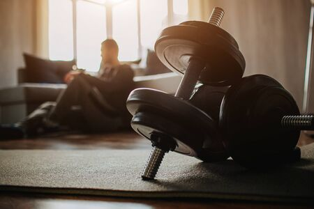 Young ordinary man go in for sport at home. Dark view on tired male preson after training sit on floor and rest. Ordinary guy after exercising. Dark dumbbells in front of picture.