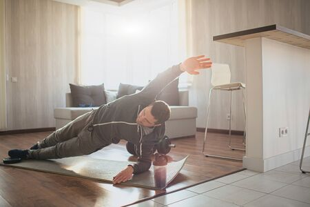 Young ordinary man go in for sport at home. Bright picture of real workout beginner stand in side plank position and hold one hand up. Ordinary guy started his training. Hardworking person in action. Foto de archivo