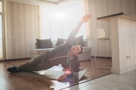 Young ordinary man go in for sport at home. Persistant freshman workout beginner stand in side plank position and look up on his stretched hand. Exercising alone in apartment. Ordinary guy on picture.