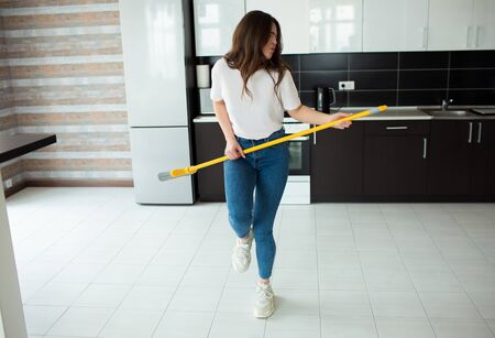 Young woman on kitchen during quarantine. Hold broom in hands as musical instrument and pretend to play on it. Dance alone after cleaning.