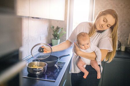 Mother holds her baby in her arms. And cooks in the kitchen. Mom speaks on the phone and is very busy. Multifunctionality concept.
