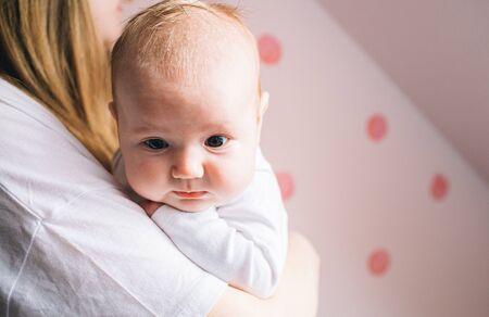 一个新出生的婴孩的画象。母亲抱着一个孩子在她的怀里。生命的第一年