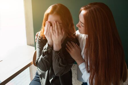 Young woman crying in a cafe covers her face with hands. Female model hugs her friend.