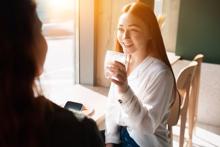Young woman holds a cup of coffee and speaks with her friend. Female model drinks coffee and sits in a cafe