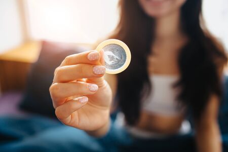 Young beautiful woman in morning bed at home. Female model hold condom in hand and show it on camera. Blurred background. Sexual safety. Stock Photo