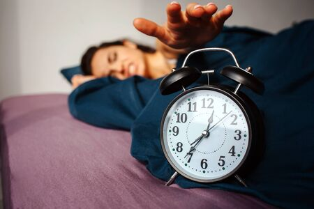 Young beautiful woman in morning bed at home. Irritated by clock ringing. Reaching it with hand. Time to wake up.