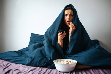 Young beautiful woman in morning bed at home. Watching scary movie alone in room. Covered with blanket. Eating popcorn and switching channels with remote control.