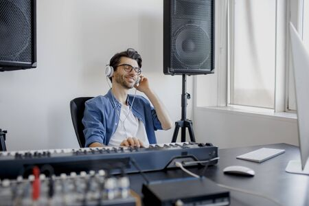 Male music arranger composing song on midi piano and audio equipment in digital recording studio. Man produce electronic soundtrack or track in project at home.