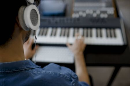 Blurred focus close-up. Male music arranger hands composing song on midi piano and audio equipment in digital recording studio. Man produce electronic soundtrack or track in project at home