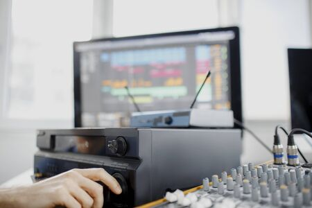 Male music arranger works with sound amplifier he is composing song on midi piano and audio equipment in digital recording studio. DJ in broadcasting studio. music, technology and equipment concept