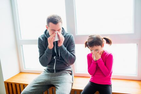 young father and his cute little daughter have handkerchief and runny nose after training on a mat indoor. ute kid and daddy have exercises near the window in her room.