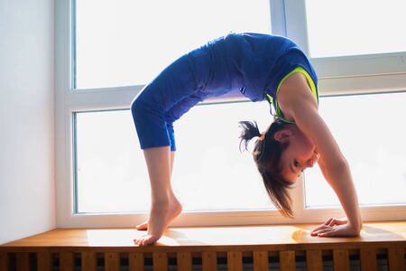 Little girl workout at home in bridge pose. ute kid is training on a wooden windowsill indoor. Little dark-haired female model in sportswear has exercises near the window in her room 版權商用圖片