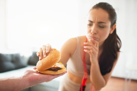 Young woman doing yoga workout in room during quarantine. Girl with red measure tape across shoulder hold upper part of burger and think. Want to eat or not. Stok Fotoğraf