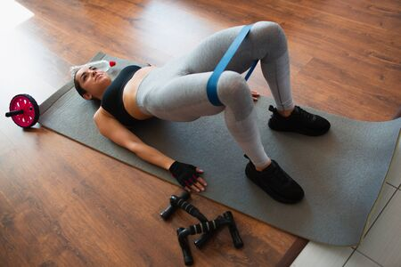 Young woman doing sport workout in room during quarantine. Lying on mat and hold body in glute bridge position. Elastic resistance band over legs. Exercising without equipment.