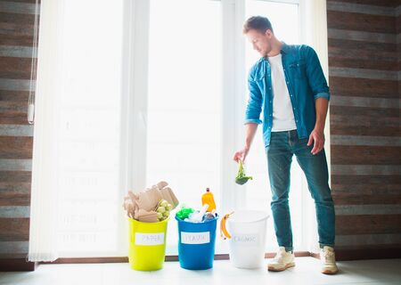 close-up concept. Sort garbage at home. There are three buckets for different types of garbage. Guy sorts waste in the kitchen