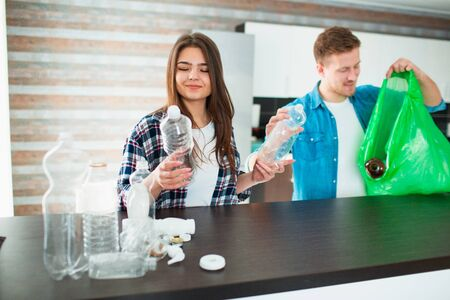 A young family sorts materials in the kitchen for recycling. Recyclable materials must be separated. Woman holds empty plastic bottles in her hands and gives them to man