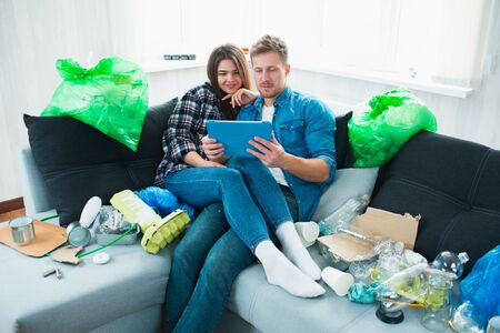 Environmental pollution concept. Silin young couple on the sofa in the living room. There is a lot of rubbish, plastic waste around. People do not notice problems with plastic pollution 스톡 콘텐츠