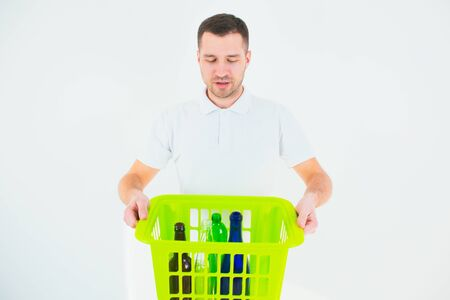 Young man isolated over white background. Guy hold green plastic basket with bottles inside it. Recycling and responcible using. No waste lifestyle.