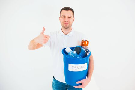Young man isolated over white background. Caucasian guy hold big thumb up and smile. Blue bucket with plastic bottles inside. Good for recycling process. No waste lifestyle and environment.
