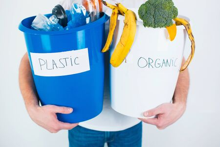 Young man isolated over white background. Cut view of a guy holding separated buckets with organic and plastic waste. Responcible using and recycling. No waste lifestyle.