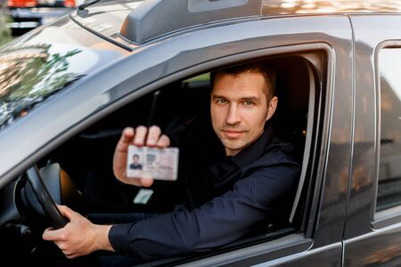A man shows a driver s license to a policeman. Businessman looking at the camera Imagens