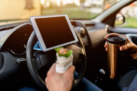 The driver watches movies or TV shows on the tablet during lunch. Stopping for a bite to eat . Man eat snack in the car and drinks coffee or tea