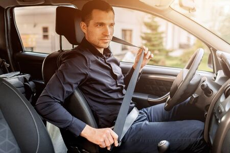 Safety driving concept. A man fastens his seat belt. Before driving