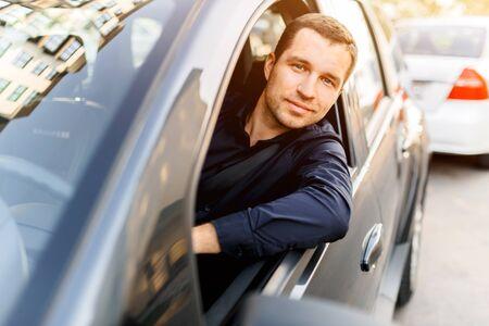 Young man in the dark swordsman driving sobsvenno car peeking out and looking at the camera