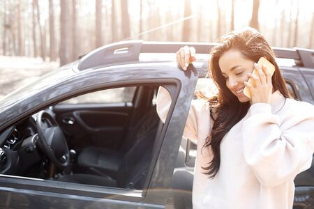 A beautiful black-haired young woman is standing near a car in a forest or park. Female models have a trip out of town on a crossover. She speaks on the phone or smartphone and holds a thermos in her hands with coffee or tea.