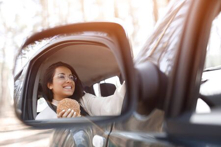 Beautiful brunette model has lunch in a car. Woman eats a hamburger and drinks coffee or tea. Food on the road concept.