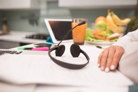 des écouteurs avec un casque sont sur la table. Lieu de travail en gros plan dans la cuisine. Une femme travaille à domicile. Il y a un ordinateur portable, un stylo, une tablette, un crayon, un cahier, des marqueurs