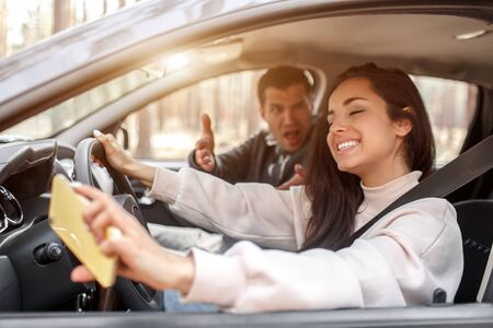 Driving instruction. A young woman learns to drive a car . Her instructor or boyfriend doesnt like the way she drives a car. But the girl is pleased with herself and does not listen to the guy. Stok Fotoğraf