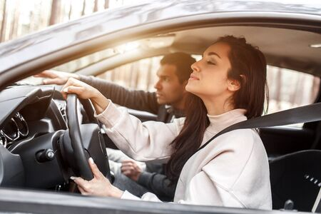 Driving instruction. A young woman learns to drive a car for the first time. Her instructor or boyfriend helps her and teaches her