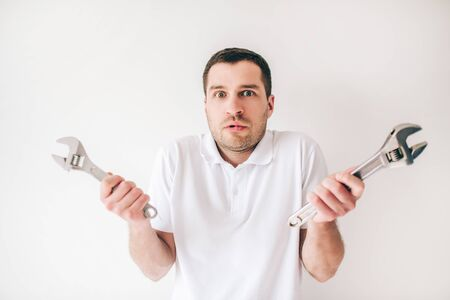Young man isolated over white background. Confused guy hold two wrenches in hands and posing on camera. Repair man or plumber.