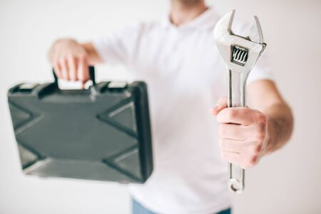 Young man isolated over white background. Cut view of guy holding box and wrench in hands. Repain man of fixing plumber.
