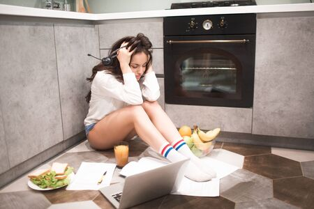 a beautiful young woman works all night in the kitchen in her house she is very tired. But still a lot of work. Working at home is difficult and tiring Stock fotó