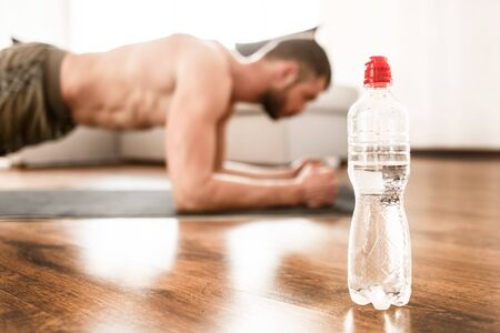water bottle close-up. Young man go in for sport at home. Cut view of t-shirtless guy sportsman with a sports figure stand in plank position. Freshman working hard on exercise.