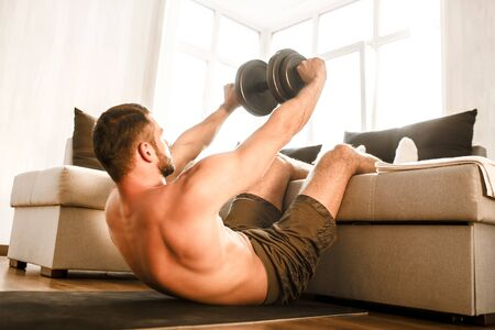 Young man doing abs exercising with a dumbbell at home on the couch. Cut view of hardwoking t-shirtless guy sportsman in workout activity at his apartment. dumbbells on pictures lying on floor.