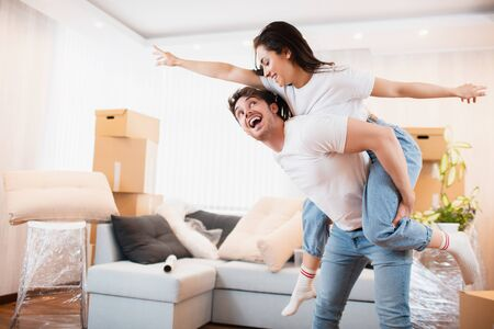 H appy husband and wife have fun swirl sway relocating to own apartment together, relocation concept. Overjoyed young couple dance in living room near cardboard boxes entertain on moving day.
