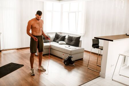 Athletic build A handsome naked torso athlete has a workout with a skipping rope at home. Sports guy without a shirt does sports in the living room Banque d'images