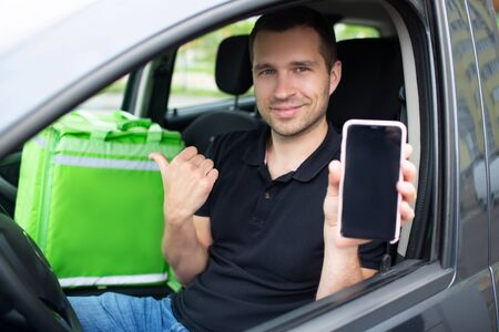 The food delivery man has a green fridge backpack. He sits in a car. He shows the screen of a smartphone with a food delivery application, looks at the camera