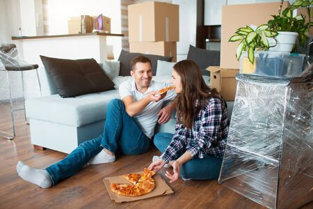 Happy family eating pizza on moving day. Picture of a young couple enjoying rest time while sitting together in the new house.
