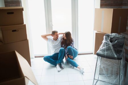 A young married couple in the living room in the house are sitting near the window. hey are happy about new home. Moving, buying a house, apartment concept.