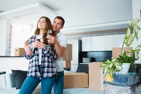 Young happy couple drinking wine, celebrating moving to new home among boxes.