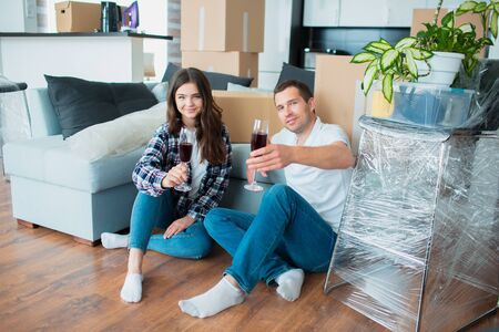 Young happy couple drinking wine, celebrating moving to new home and sitting among boxes. Banque d'images