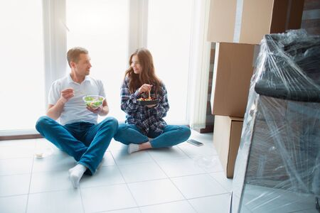 A young married couple in the living room in the house are sitting near the window and eat the first time in a new house. hey are happy about new home. Moving, buying a house, apartment concept.