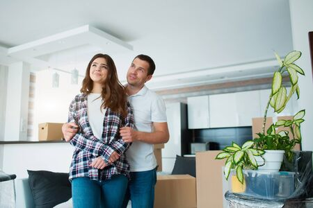 A young married couple in the living room in the house stand near unpacked boxes. hey are happy about new home. Moving, buying a house, apartment concept. Banque d'images