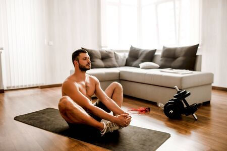 Athletic build A handsome naked torso athlete has a workout at home. Sports guy without a shirt has a stretch on a yoga mat in the living room. Banque d'images