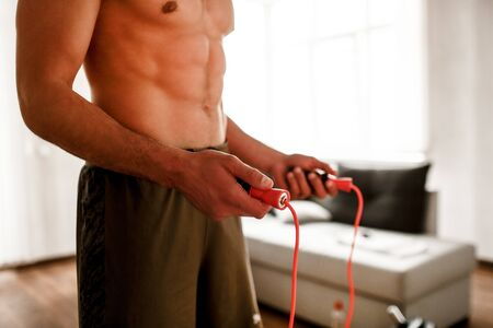 Athletic build A handsome naked torso athlete has a workout with a skipping rope at home. Sports guy without a shirt does sports in the living room. Close-up concept
