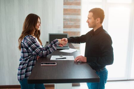 Realtor, broker or landlord shows an apartment to a young woman. She is going to sign a lease agreement with him. Estate agent shaking hands with customer after contract signature